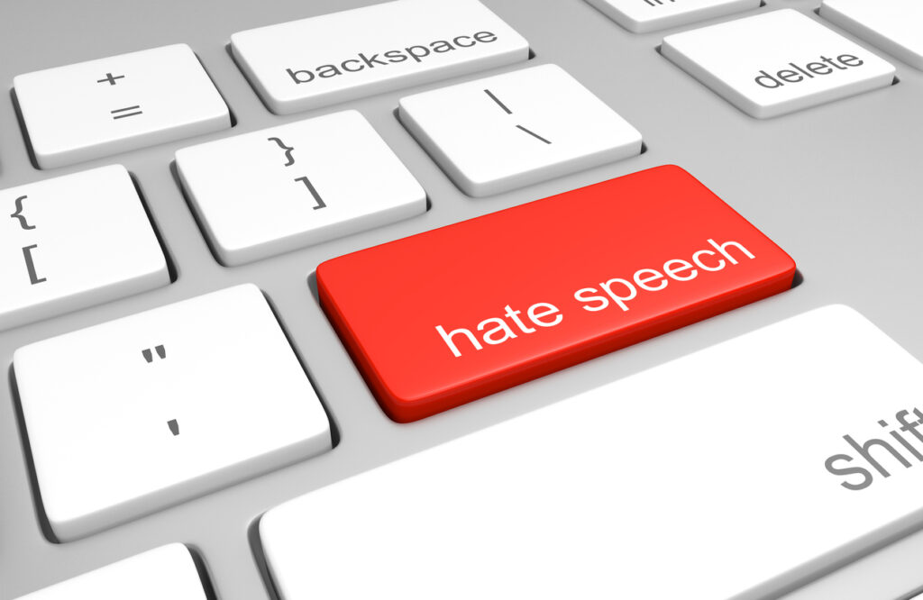 3D render of a computer keyboard with one key labeled for hate speech, representing discriminatory messages that plague online message boards and comment areas.